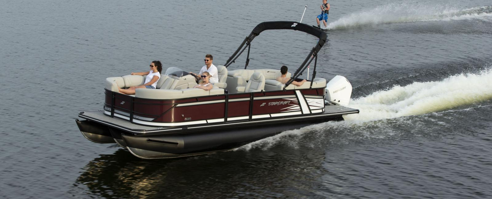 Expensive pontoon boat towing water skier