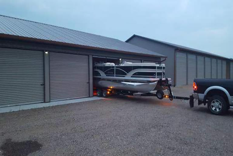 Pontoon boat being towed out of garage on trailer