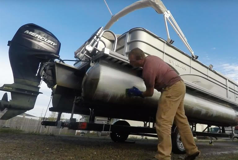 Guy cleaning pontoon boat